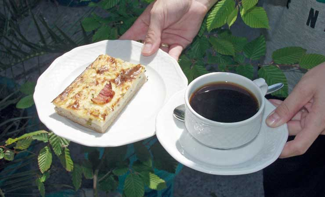 Hände halten eine Tasse Kaffee und einen Teller mit Kuchen