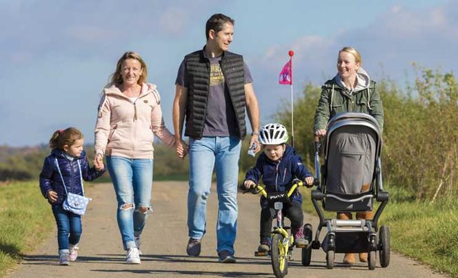 Familie mit Kleinkind auf dem Rad und einem Kinderwagen ist draußen bei Sonnenschein unterwegs
