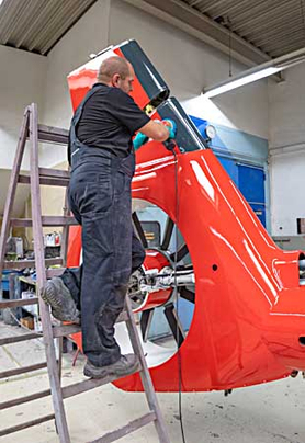 Arbeiter auf einer Leiter lackiert ein großes Hubschrauberteil