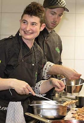 Zwei Köche hantieren in einer Küche mit Schüsseln