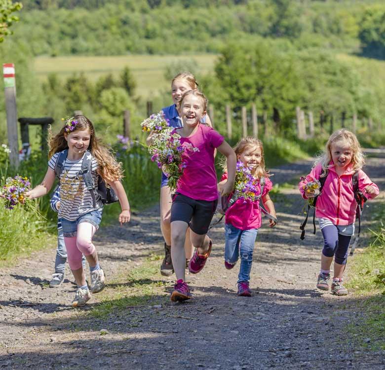 Fünf Mädchen haben im Feld Blumen gepflückt und laufen einen Feldweg entlang