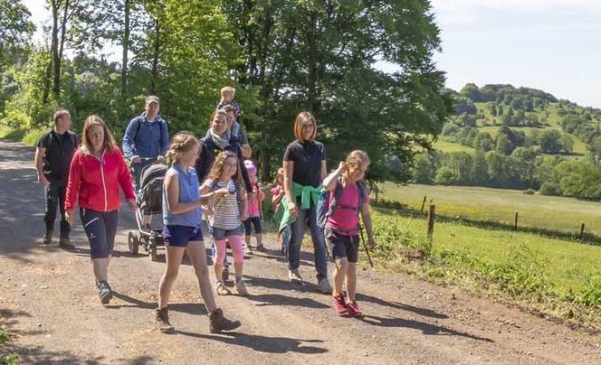 Eine Gruppe Wanderer, Erwachsene und Kinder, auf einem Feldweg im Grünen