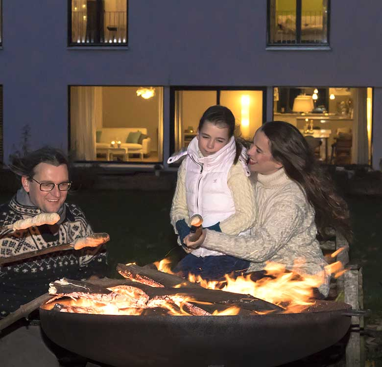 Eine Familie im Dunkeln, backt Stockbrot am Lagerfeuer vor dem Haus