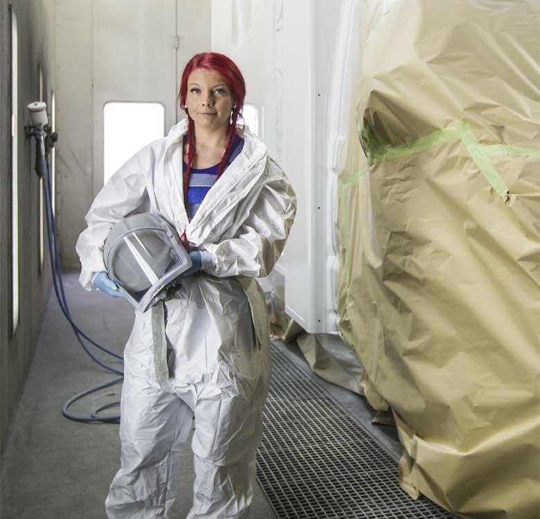 Eine Autolackiererin im Schutzanzug neben einem eingepackten Auto